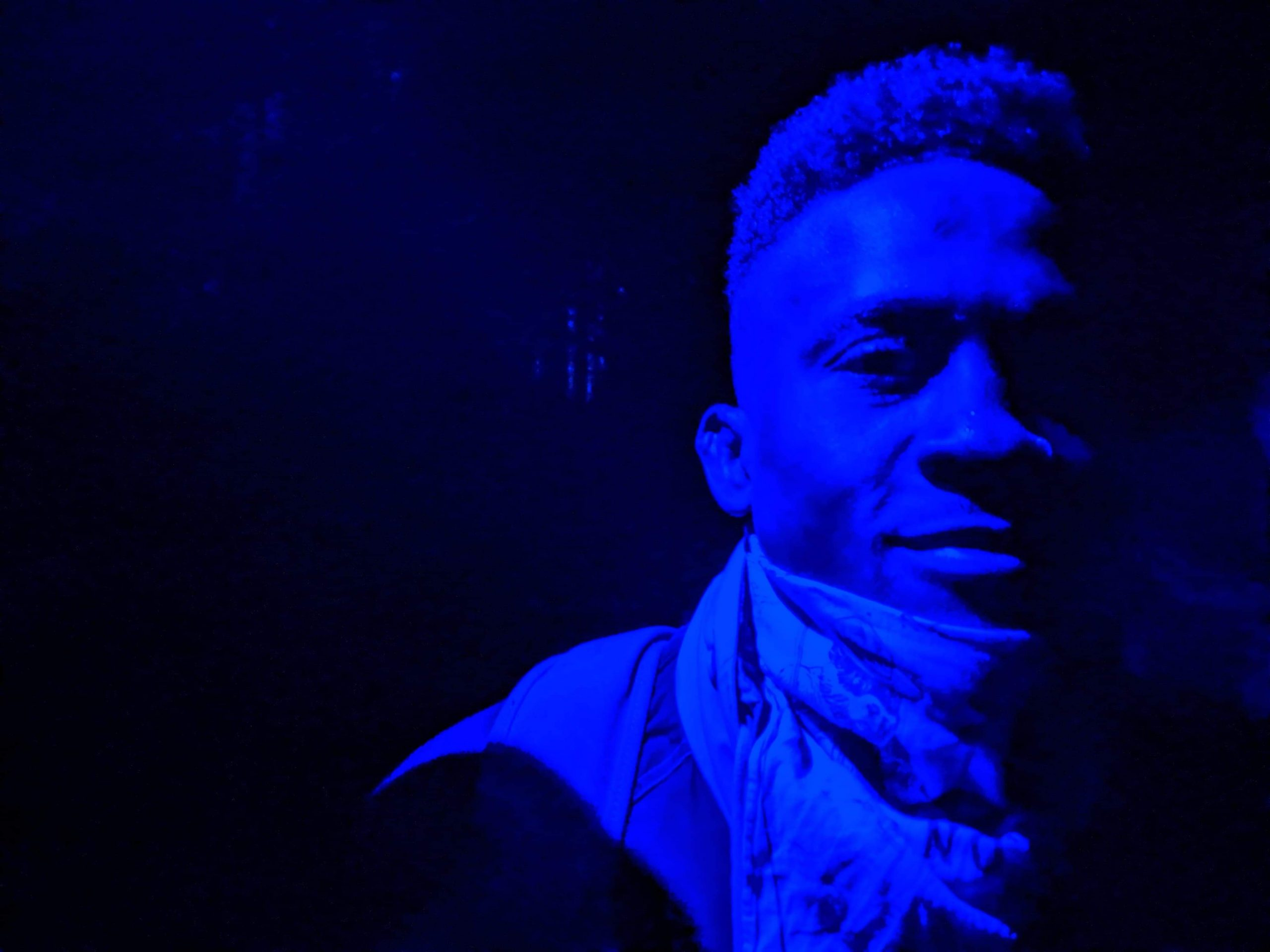 "Bellingham rapper Jordan ""The Rhetorician"" Moss illuminated in blue light."