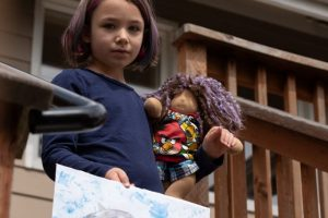Naima shows her drawing which she submitted for a prize and wone the doll in her hands for it. Photo by Emily Porter