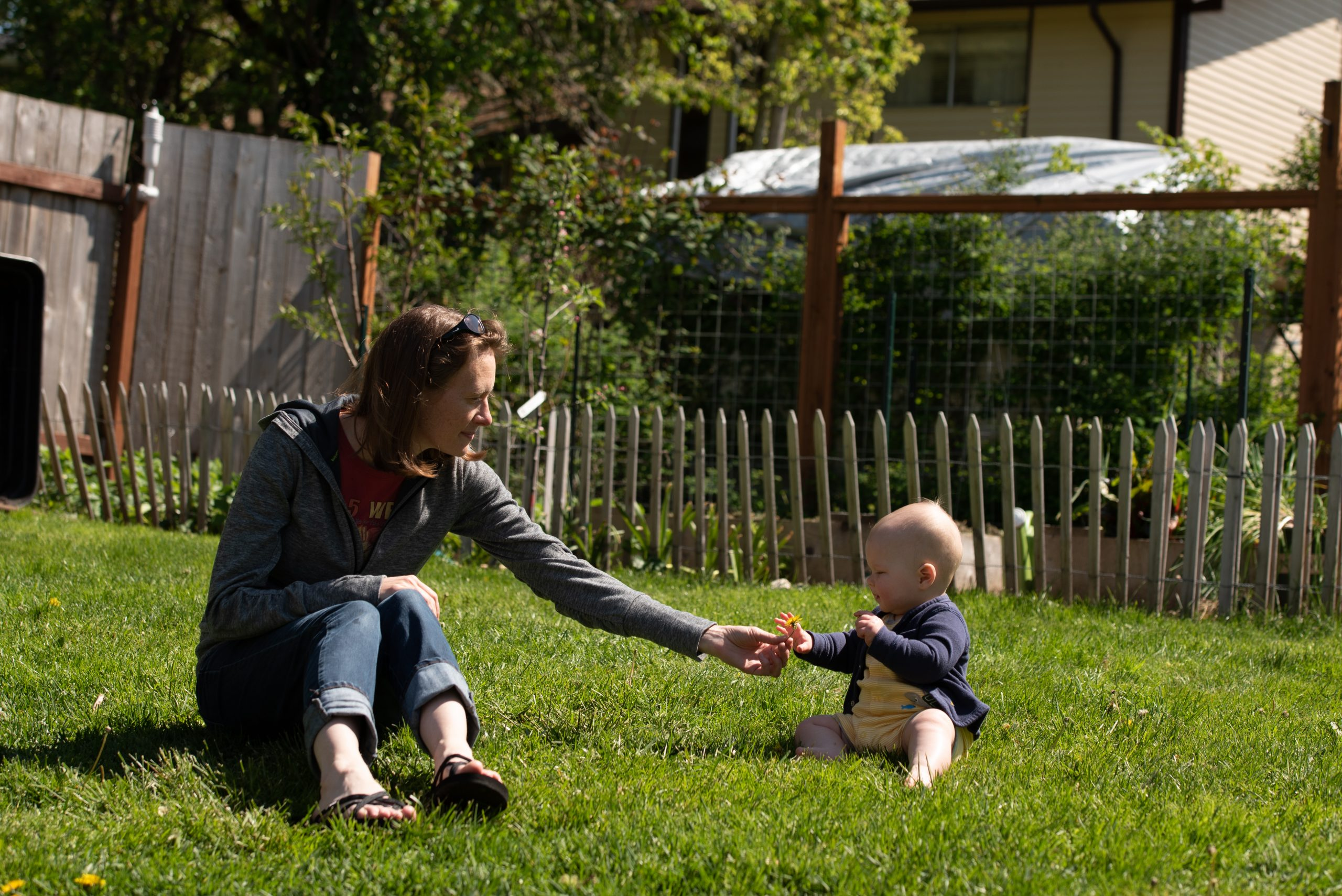 Kristin Page and her baby Fern play in their backyard that is filled with herbs, chickens, and vegetables. Photo by Emily Porter