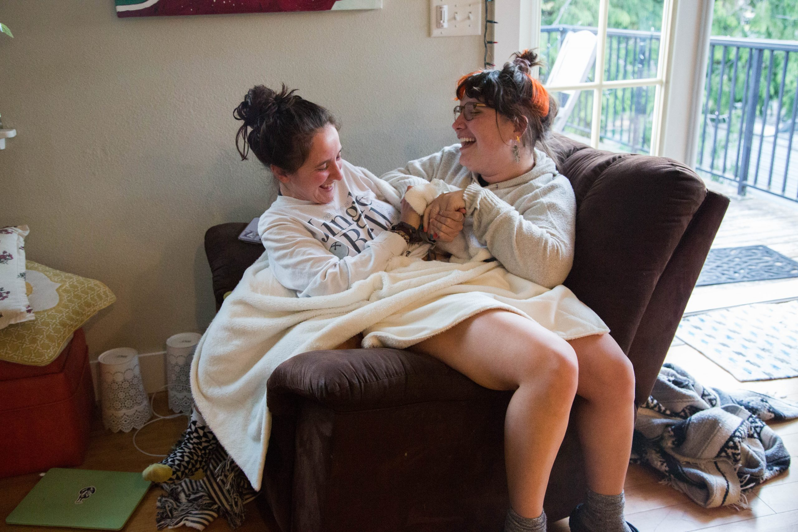 Jordan Coady and Chloe Fleuret laugh while sitting together on a recliner at home. The time at home has strengthened their relationship, both as roommates and friends.
