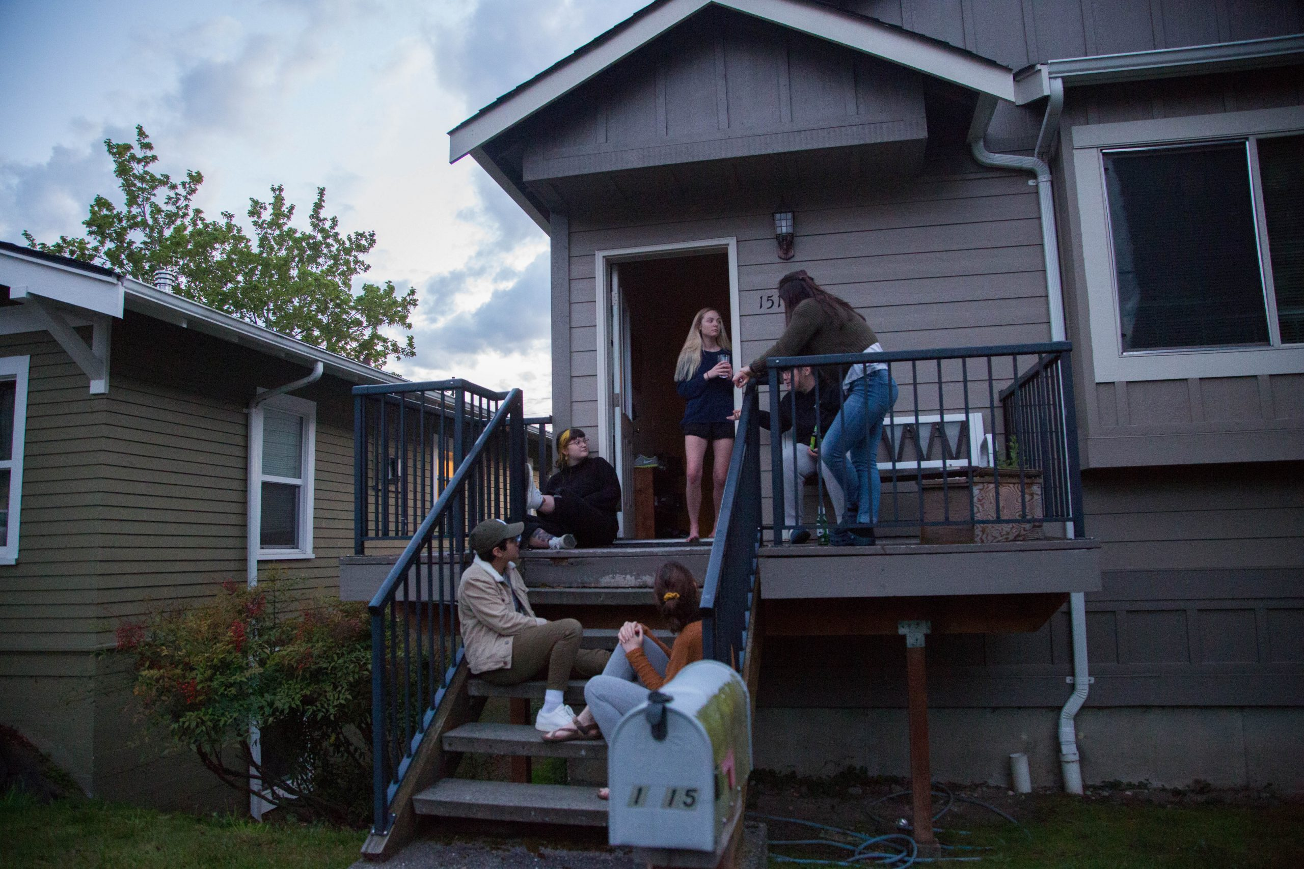 Residents of 1515 Franklin St gather on their front porch with friends. Hanging out at a distance has been important in keeping sane during quarantine.