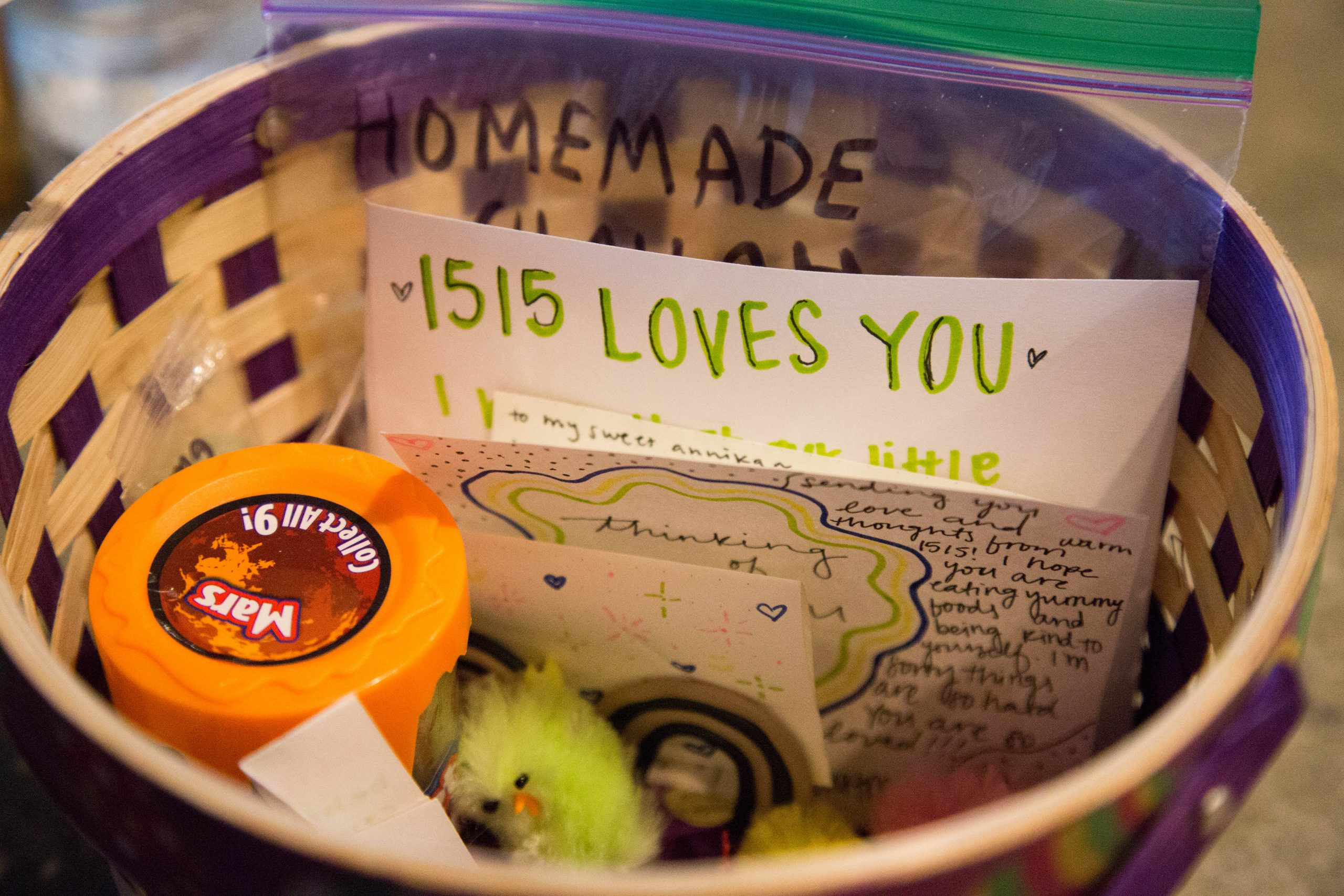 """A basket with notes and gifts sits on a table, a note reads """"1515 Loves You"""""""