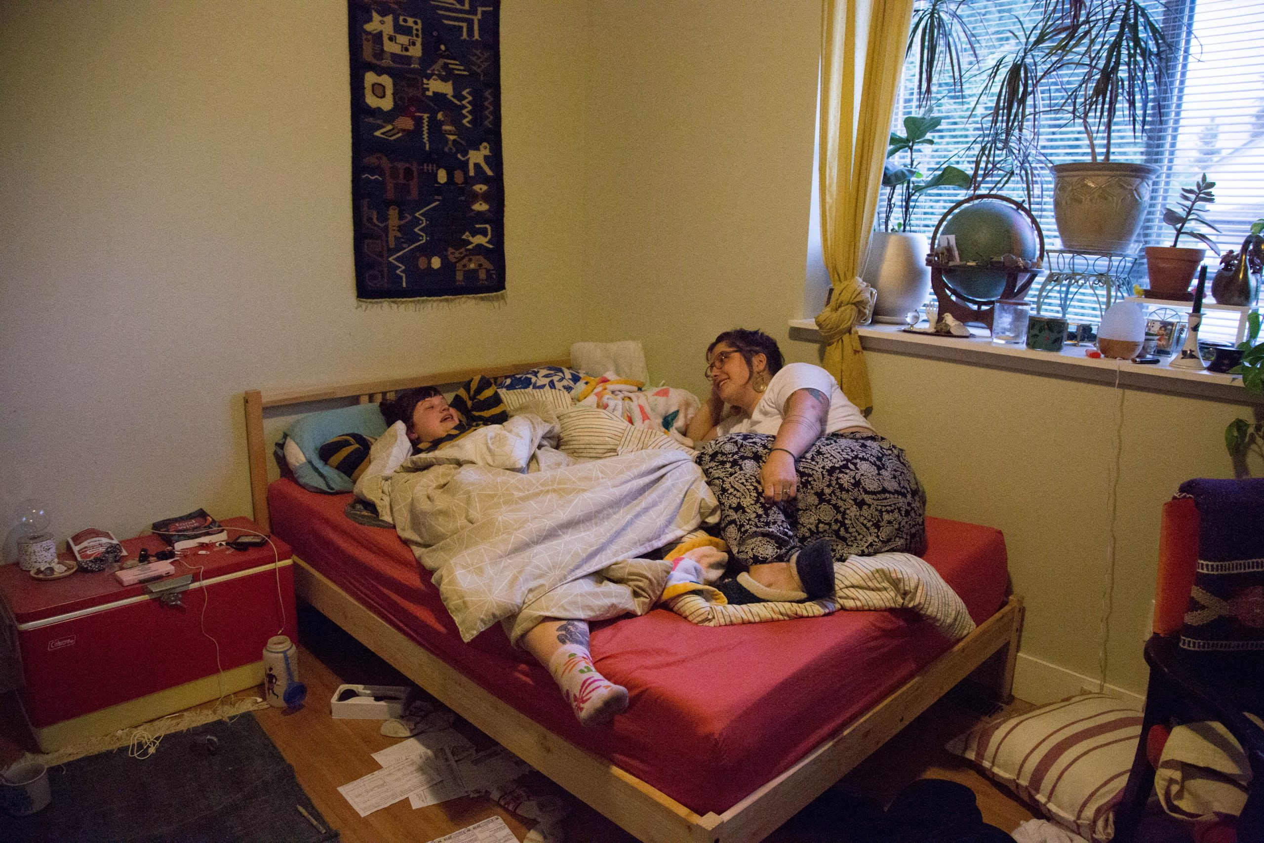 Two girls lie in a bed together, one under blankets the other on top.
